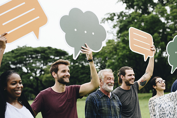 Happy diverse people holding colorful speech bubbles